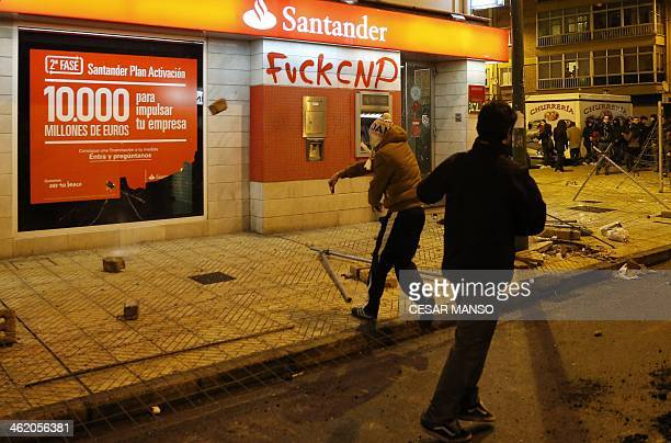 A demonstrators throws a brick at a bank store front during a protest against imminent construction works to revamp Vitoria street the city's main...