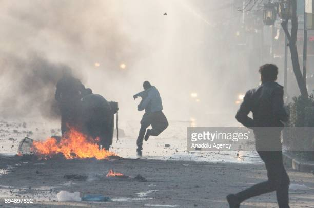A demonstrators throws a rock as they burn tires and block a road with a trash bin while they clash with riot police within antigovernment protests...
