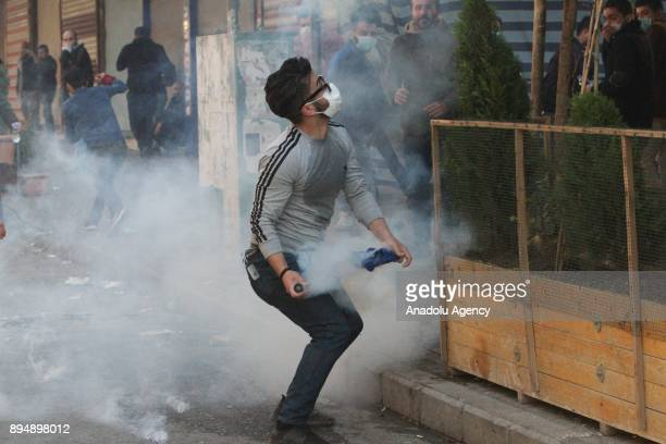 A demonstrators throws a tear gas can back at riot police as they clash within antigovernment protests in Sulaymaniyah Iraq on December 18 2017...