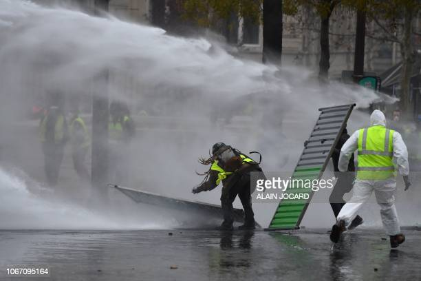 Demonstrators try to avoid the stream of water cannons of the riot police during a protest of Yellow Vests against rising oil prices and living costs...