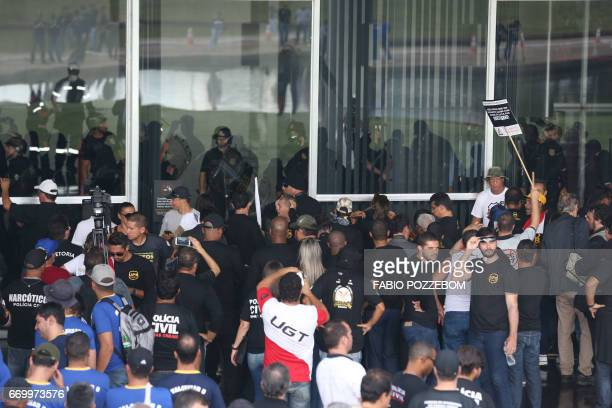 Demonstrators try to force their entry into the building during a protest by Police Union members against the pension system reform in front of the...