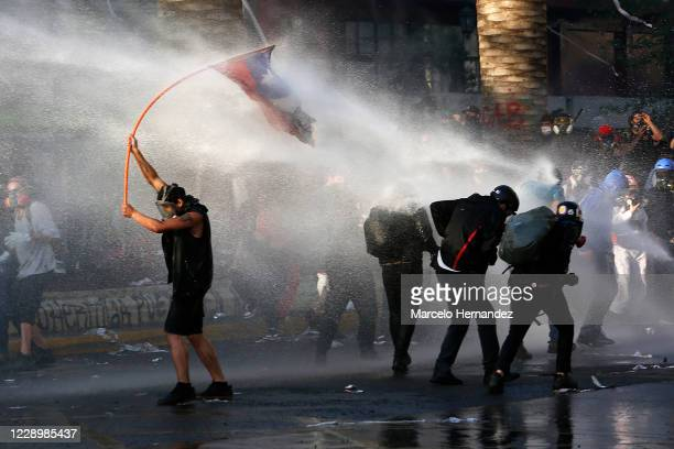 Demonstrators try to keep stand in front of a stream of water shot by a water cannon vehicle during a protest against a wide range of issues...
