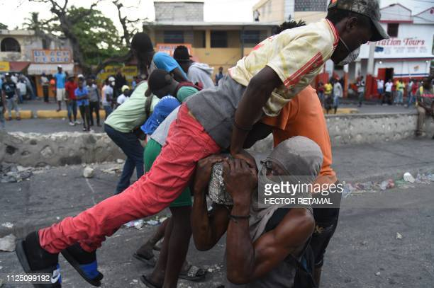 Demonstrators try to place a barricade during clashes with Haitian police in PortauPrince February 15 on the ninth day of protests against Haitian...