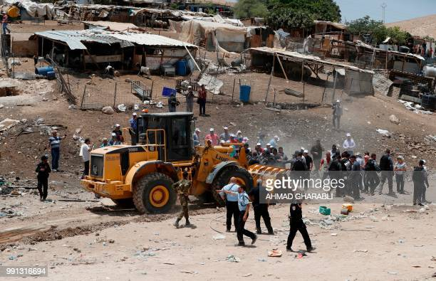 Demonstrators try to prevent a tractor from passing through in the Palestinian Bedouin village of Khan alAhmar east of Jerusalem in the occupied West...