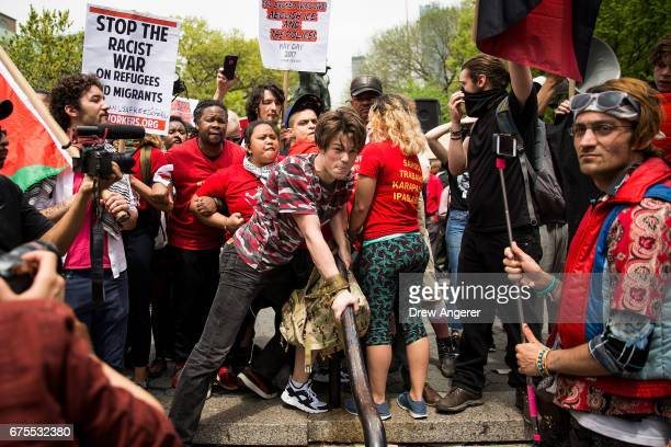 Demonstrators try to remove a counterprotestor whom they accused of making racist comments during a May Day rally in Union Square May 1 2017 in New...