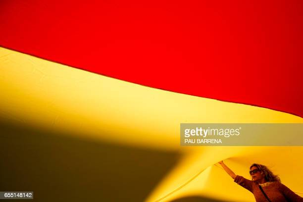 TOPSHOT Demonstrators unfold a big Spanish flag during a demonstration called by 'Sociedat Civil Catalana' to support the unity of Spain in Barcelona...