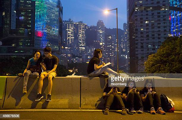 Demonstrators use their mobile phones while sitting on Connaught Road Central in Hong Kong China on Sunday Oct 5 2014 Hong Kong student protesters...