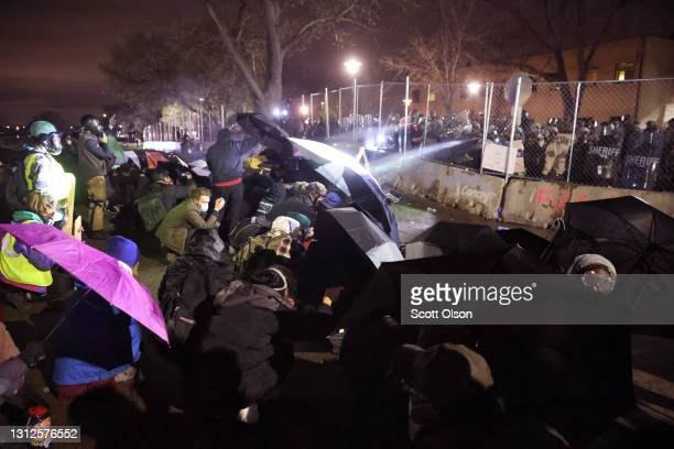 Demonstrators use umbrellas for protection as police fire pepper spray and rubber bullets during a protest outside of the Brooklyn Center police...