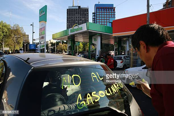Demonstrators use window paint markers on the windows of passing vehicles during a protest against the gasoline price hike near a Hidrosina gas...