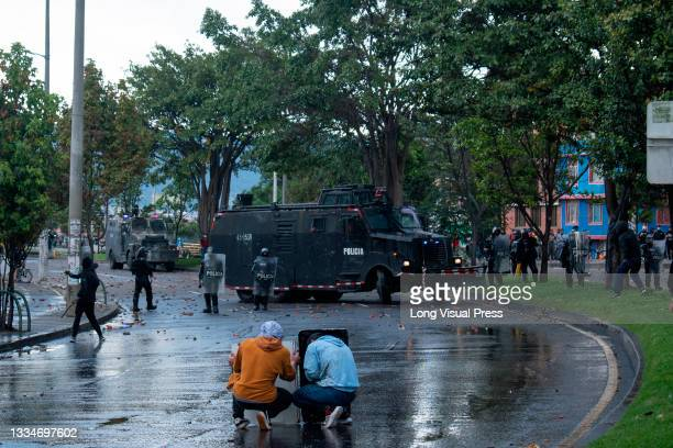 Demonstrators using wooden doors cover from water and tear gas canisters shot by a Colombia's riot police armored truck during anti-government that...