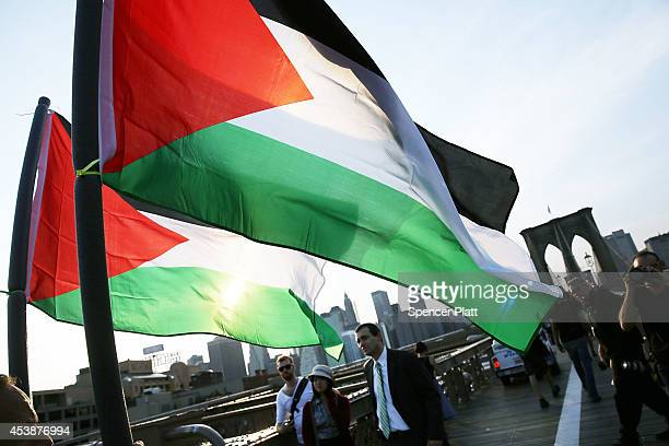 Demonstrators walk across the Brooklyn Bridge while protesting against Israel's continued military campaign in Gaza on August 20 2014 in New York...