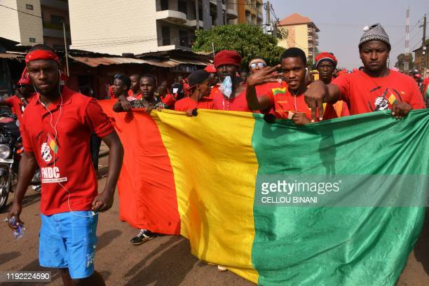 Demonstrators walk behind a giant Guinea's national flag on January 6 2020 in Conakry as they take part in an antigovernment rally to protest against...