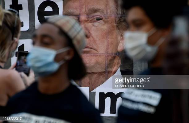 Demonstrators walk by a sign calling to vote out racism with a picture of President Donald Trump during a peaceful protest against police brutality...