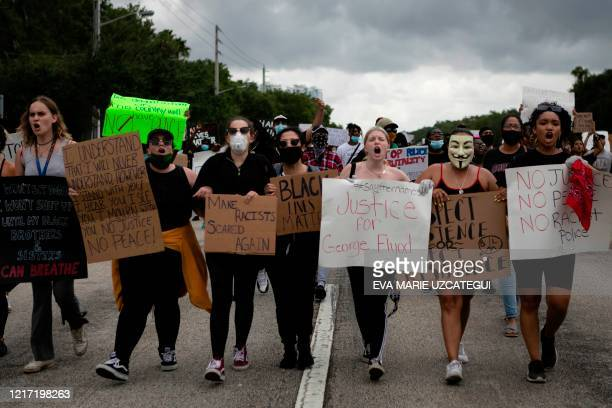 Demonstrators walk holding signs during a protest against police brutality and the recent death of George Floyd in Sunrise, Florida on June 02, 2020....