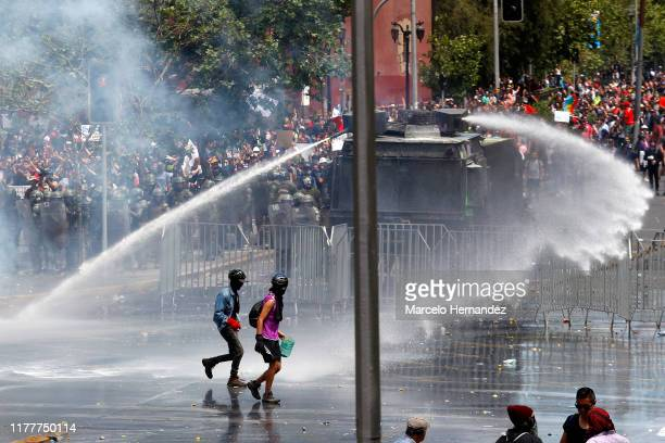 Demonstrators walk out from the water cannon fired by riot police during the sixth day of protest against President Sebastian Piñera on October 23,...