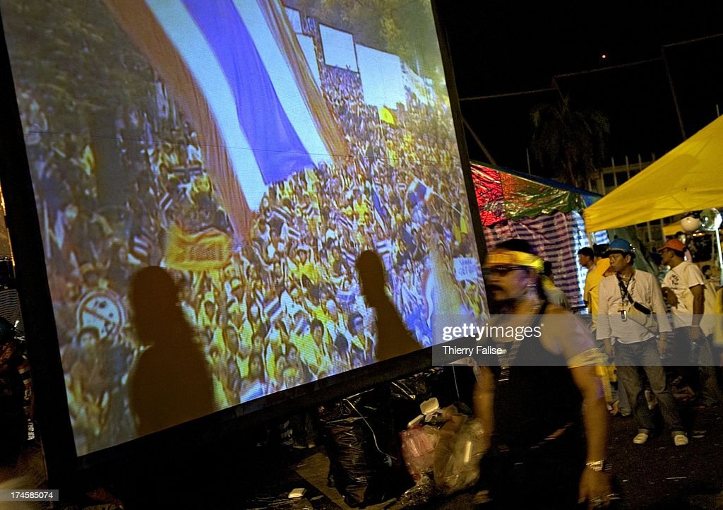 Demonstrators walk past a giant screen. Thousands of... : News Photo