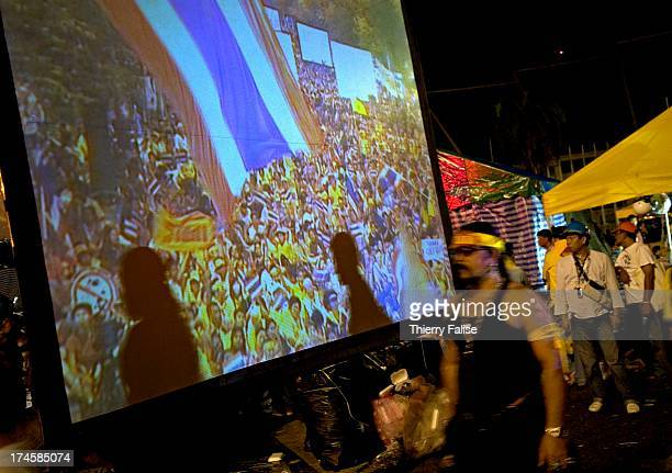 Demonstrators walk past a giant screen Thousands of demonstrators have defied warnings of a crackdown from the Thai Prime minister Samak Sundaravej...
