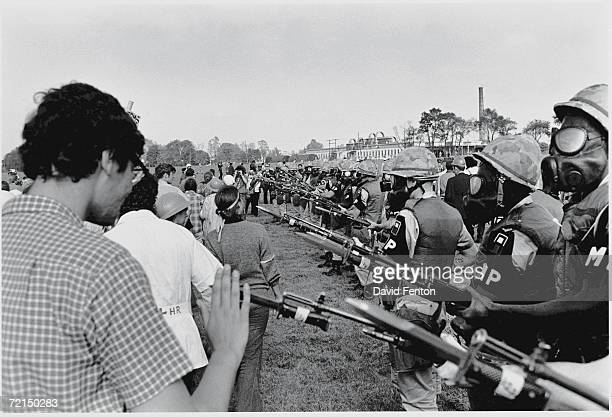 Demonstrators walk past a line of armed MPs from the United States First Army wearing gas masks and carrying rifles with fixed bayonets Fort Dix New...