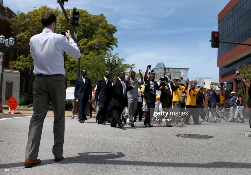 Demonstrators walk through the street near the Buzz Westfall Justice Center where a grand jury will begin looking at the circumstances surrounding the fatal police shooting of an unarmed teenager Michael Brown on August 21, 2014 in Clayton, Missouri. The protesters are asking that justice be brought against the police officer that shot Brown on August 9.
