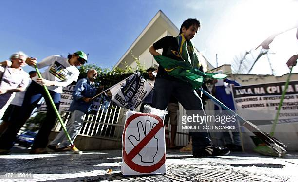 Demonstrators wash the sidewalk in front of the Lula Institute as a way to protest against corruption in Sao Paulo Brazil on June 14 2015 A Brazilian...