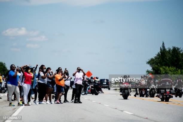 Demonstrators watch a parade of passing motorcyclists riding in honor of Ahmaud Arbery at Sidney Lanier Park on May 9, 2020 in Brunswick, Georgia....