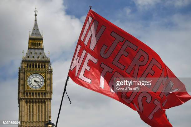 Demonstrators wave a flag showing support for Labour Party leader Jeremy Corbyn during the 'Not One Day More' march at Parliament Square on July 1...