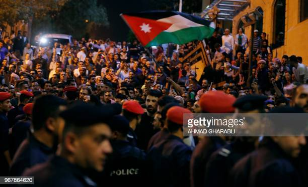 Demonstrators wave a Jordanian flags in front of Jordanian policemen during a protest near the prime minister's office in Amman Jordan on June 5 2018...
