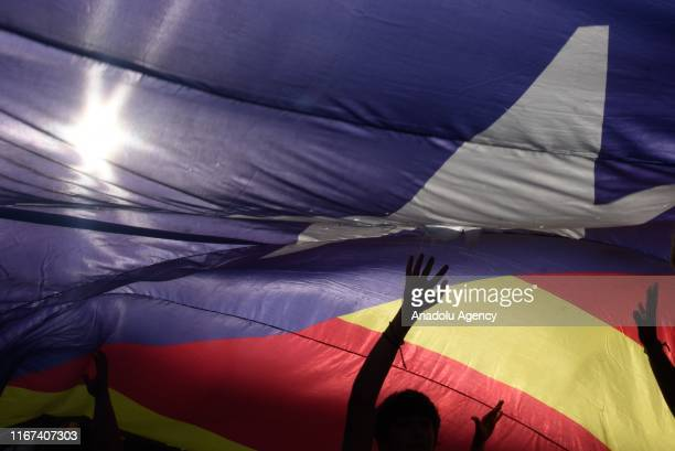 Demonstrators wave a massive proindependence Catalan Estelada flag during Catalonia's national day known as Diada Nacional de Catalunya at Plaza...