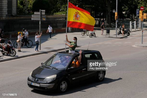 """Demonstrators wave a Spanish flag from inside a car during a """"caravan for Spain and its freedom"""" protest by far-right party Vox in Barcelona on May..."""