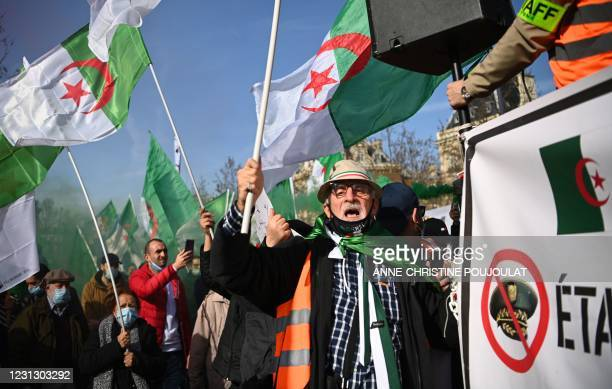 Demonstrators wave Algerian national flags during a rally in Paris on February 21 in support of the Hirak anti-government movement in Algeria. - The...