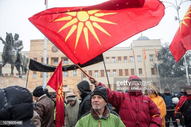 Demonstrators wave an old Macedonian flag during a protest against a process of renaming the country's name in front of the Parliament building in...