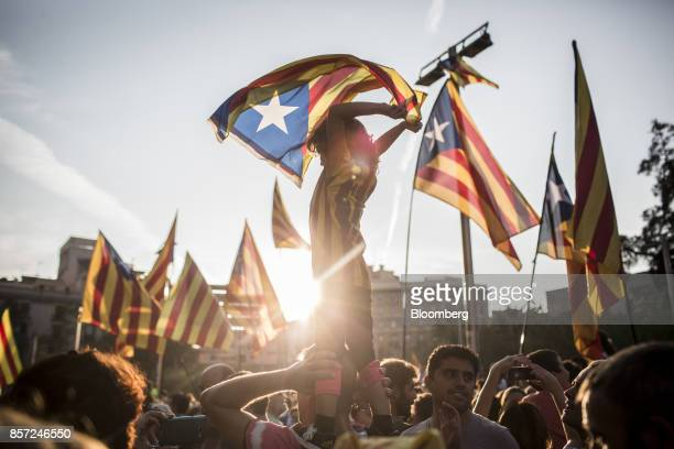 Demonstrators wave Catalan flags while marching through the city to protest against alleged police violence during Sunday's illegal referendum vote...