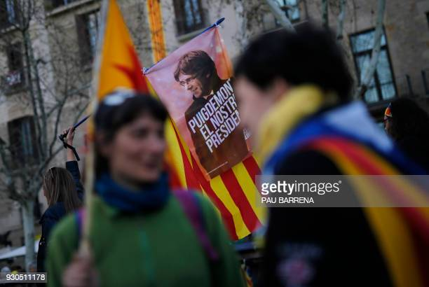 Demonstrators wave Catalan proindependence 'Estelada' flags with an image depicting deposed Catalan president Carles Puigdemont during a protest to...