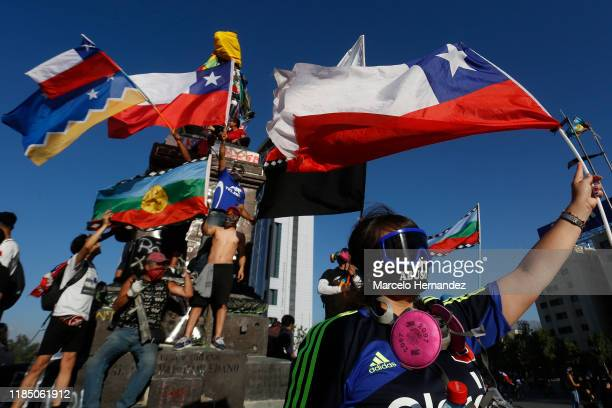Demonstrators wave Chilean and wenufoye at Plaza Italia during a protest against government president Sebastian Piñera on November 27 2019 in...