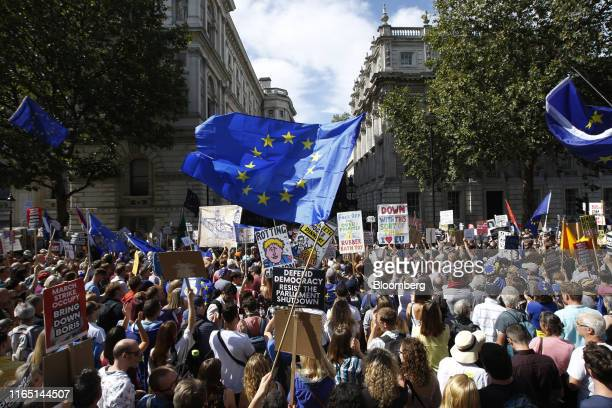 Demonstrators wave European Union flags and hold placards outside Downing Street during a protest against the proroguing of parliament in London UK...