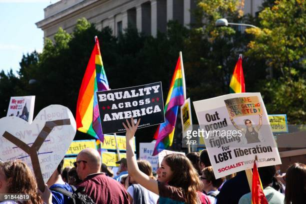 Demonstrators wave flags and banners in Washington on October 11 2009 as tens of thousands of gay activists marched to demand civil rights a day...