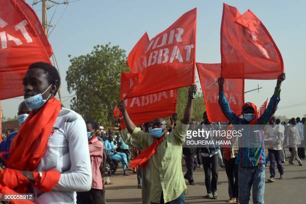 Demonstrators wave flags and brandish panels as they take part a march in Niamey on December 31 2017 to protest against the Niger's 2018 budget law /...