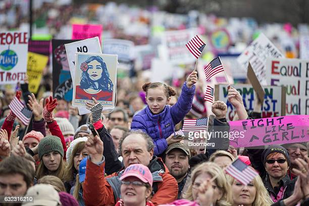 Demonstrators wave flags and hold signs during the Boston Women's March in Boston Massachusetts US on Saturday Jan 21 2017 Hundreds of demonstrations...