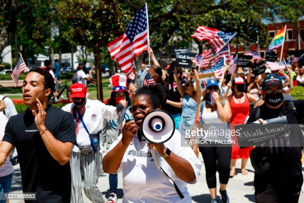Demonstrators wave flags as they march in support of the US president during a WalkAway rally on August 8, 2020 in Beverly Hills, California.