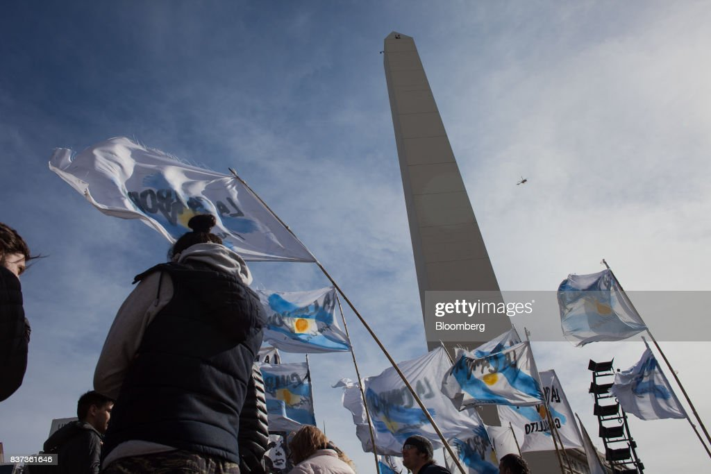 Demonstrators wave flags during a protest in Buenos Aires, Argentina, on Tuesday, Aug. 22, 2017. Union groups protested Argentinean President Mauricio Marcri's economic policies. Photographer: Erica Canepa/Bloomberg via Getty Images