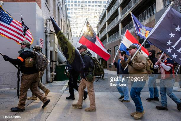 Demonstrators wave flags during the Virginia Citizens Defense League Lobby Day rally at the state capitol in Richmond Virginia US on Monday Jan 20...