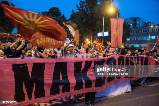 Demonstrators wave flags in front of the parliament building in Skopje on June 13 2018 during a protest against the new name of the country Greeks...