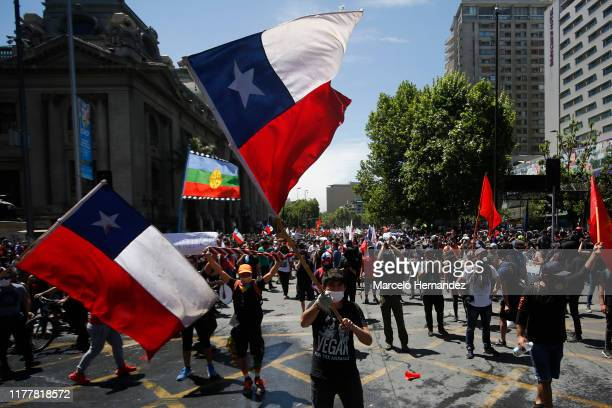 Demonstrators wave flags of Chile during the sixth day of protest against President Sebastian Piñera on October 23 2019 in Santiago Chile Although...