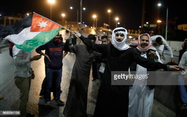 Demonstrators wave Jordanian flags during a protest near the prime minister's office in Amman Jordan on June 6 2018 Jordanian Prime Minister Hani...