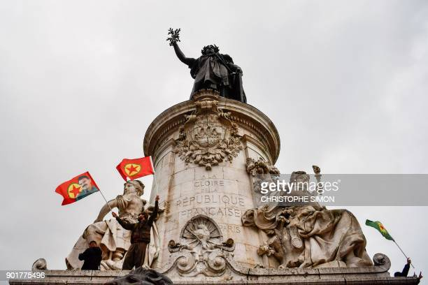 Demonstrators wave Kurdistan Worker's Party flags on the statue of Marianne on the Place de la Republique during a demonstration in Paris on January...