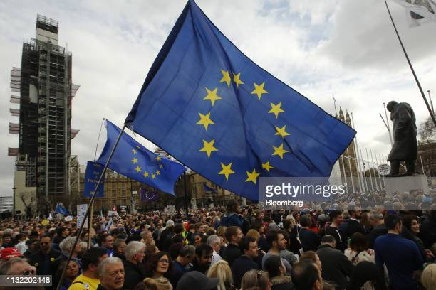 Demonstrators wave large European Union flags as they stand on Parliament Square during the antiBrexit People's Vote rally in London UK on Saturday...