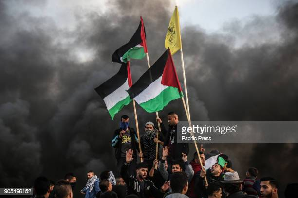 Demonstrators wave Palestinian flags during clashes with Israeli troops near the border with Israel in the east of Gaza City