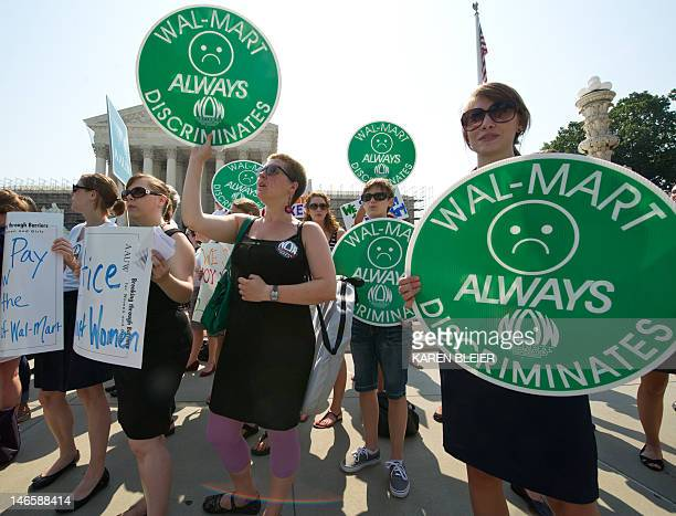 Demonstrators wave placards during a rally to mark the oneyear anniversary of the WalMart v Dukes decision the largest class action lawsuit in...