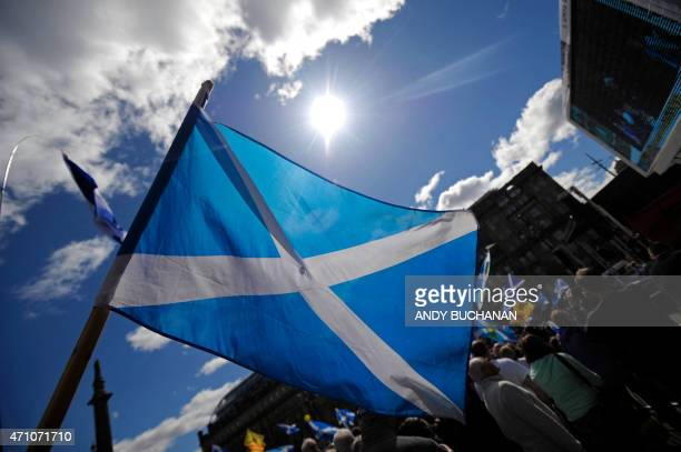 Demonstrators wave Saltire flags, the national flag of Scotland, during a pro-independence rally in Glasgow, Scotland on April 25 urging the Scots to...