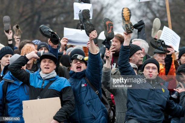 Demonstrators wave shoes as a sign of disrespect during a demonstration against German President Christian Wulff in front the Bellevue Castle on...